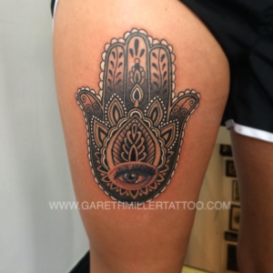 Black and grey hamsa on the thigh with dotwork