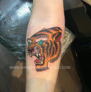 Traditional tiger head tattoo on the forearm